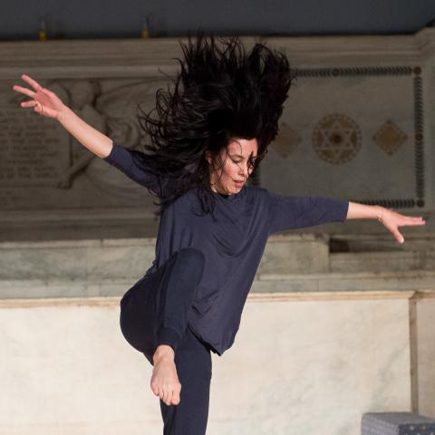 A dancer dance lands on her foot, hair blowing up away from her face.