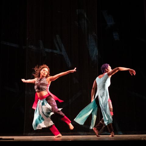 Two dancers twirl away from each other.