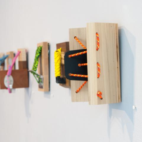Wall mounted sculptures with yarn and string tethered to wood blocks.