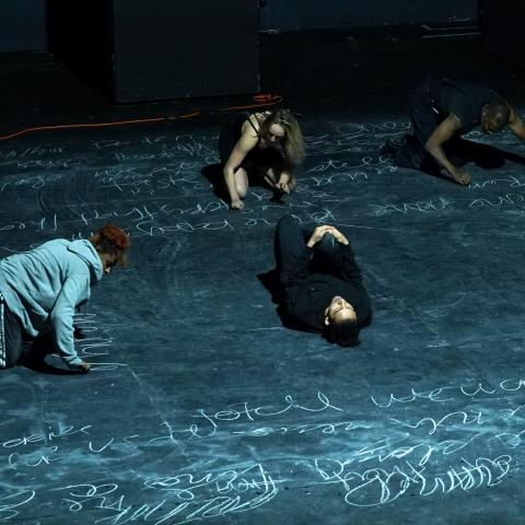 Four dancers perform on the floor of the stage.