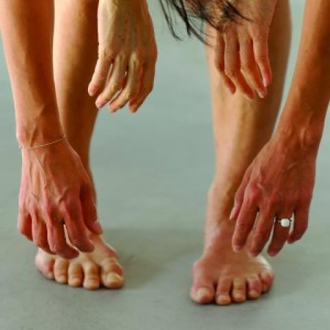 Four sets of hands hang over a pair of legs and feet.
