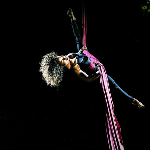 In a black void, a black woman with an afro gives an aerial performance with fabric.