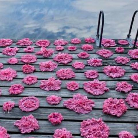 Pink paper flowers on a deck.