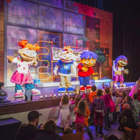 Actors dressed in full body costumes, with oversized heads perform on a stage decorated in bright colors.