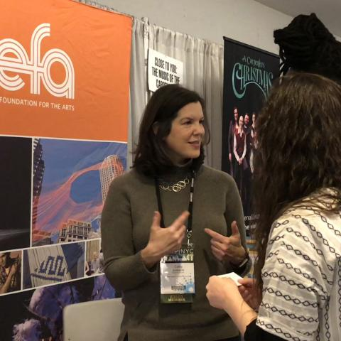 Image: Cathy Edwards speaks to attendees at APAP 2018. NEFA's orange banner is in the background.
