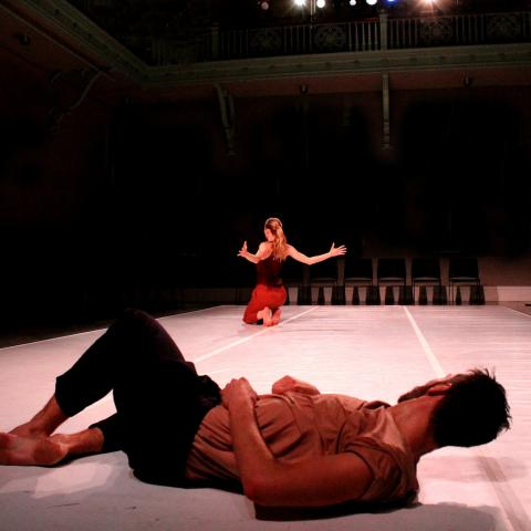 In the foreground, a male dancers lays on the floor watching a female dancer, on her feet in the background.