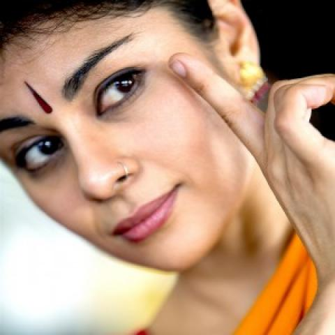 A woman with a bindi touches her pointer finger next to her eye