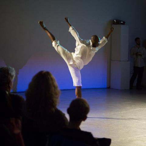 a lanky dancer dressed all in white sprawls through the air in front of a projector