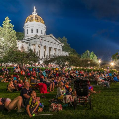 A crowd lounging on the lawn of the Vermont state capitol building