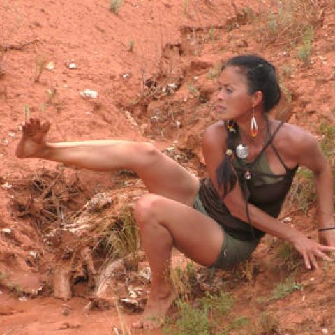 In a ditch in the desert, a woman leans on her hands and lifts her foot up as she looks at her toe,