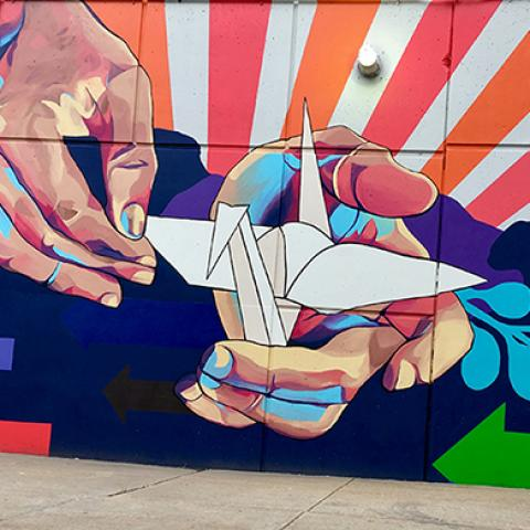A mural of two hands holding an origami swan, with rays of red and orange sunsetting behind.