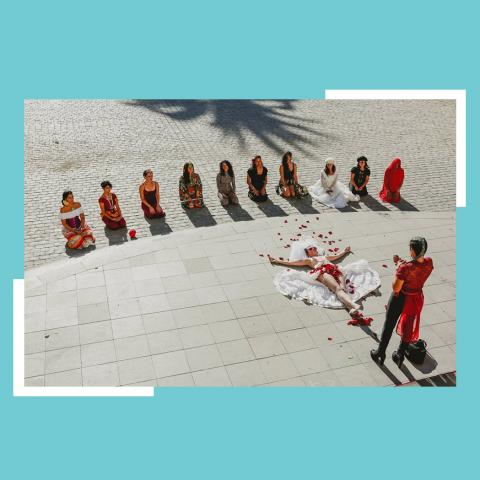 Twelve women, kneeling in a line, watch as a woman lies on the outdoor stone ground and another woman throws petals over her body. They're all in reds and whites.