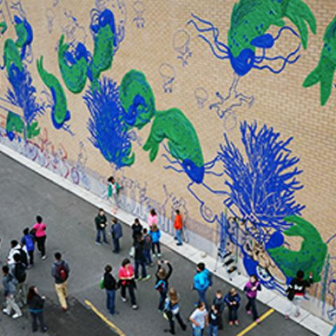 A crowd looks at a wall covered in blue and green graffiti made of tape.