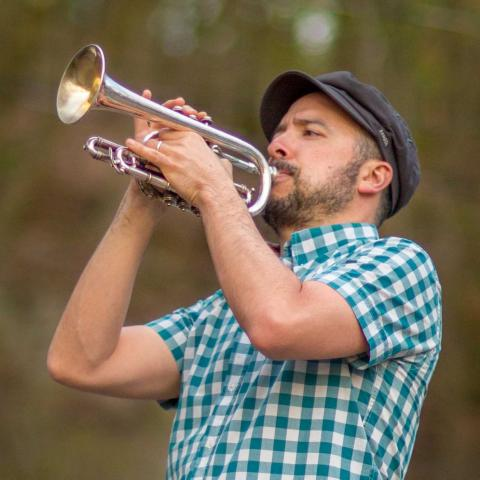 A man in a plaid shirt playing the trumpet outside with trees in the background