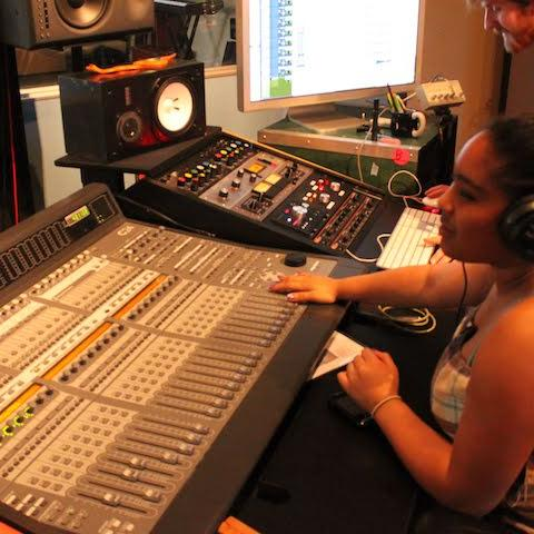 A few sound engineers are seated in a recording booth in front of a complex looking soundboard