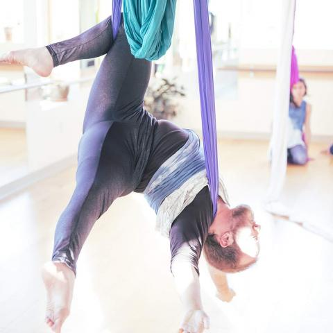 Toby suspended upside down in aerial silks in a brightly lit studio