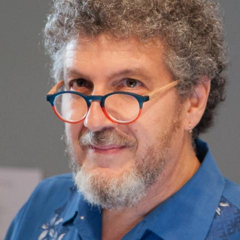 A man with curly hair and a beard wearing a blue shirt and colorful round glasses