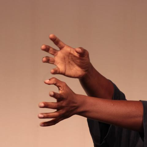 A black person with short green hair wearing a black top reaches, with hands flexed, from the left side of the image