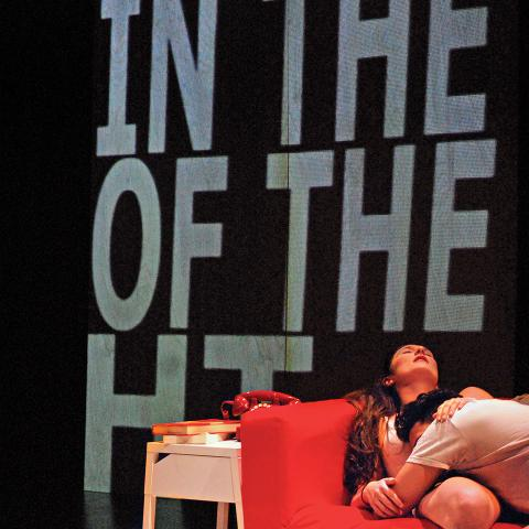 A man and a woman cuddle on a red couch, in front of screens with giant text on them.