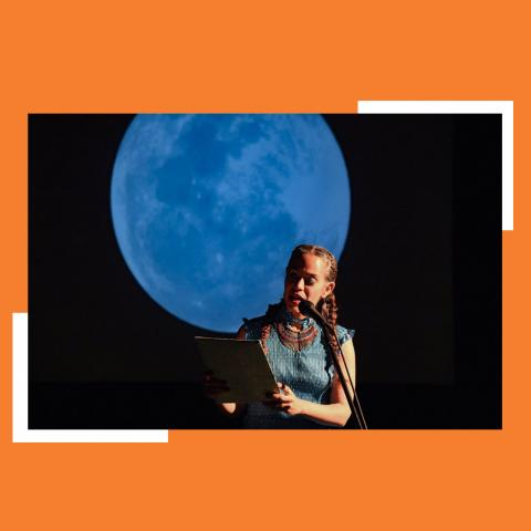In front of a large projection of the blue full moon, Yara reads into a microphone.