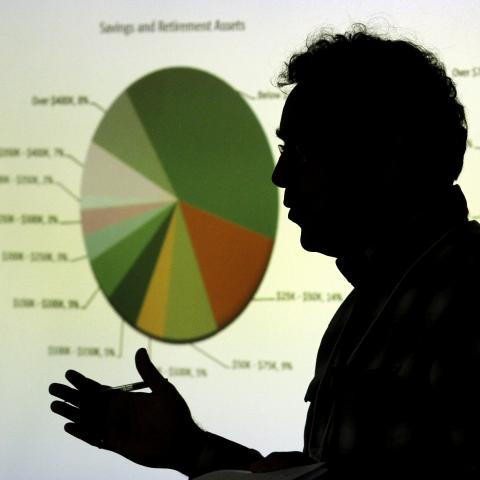 Silhouette of a man giving a presentation in front of a projection of pie charts/graphs.