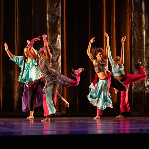 On a stage, five dancers wear color costumes.