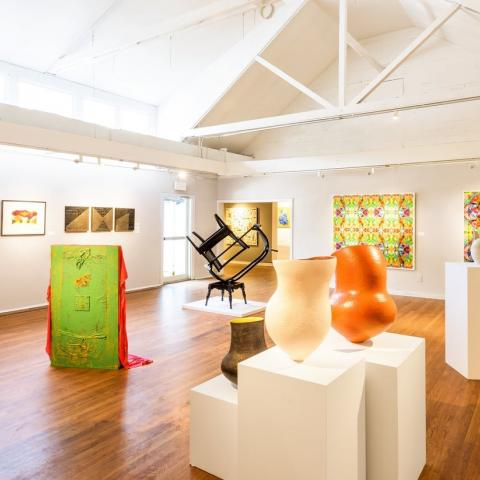 A bright, white gallery space with contemporary art.
