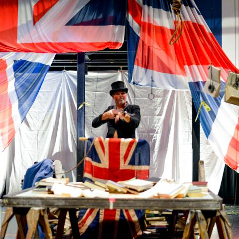 Nora, in a top hat, performs on a stage with British flags.