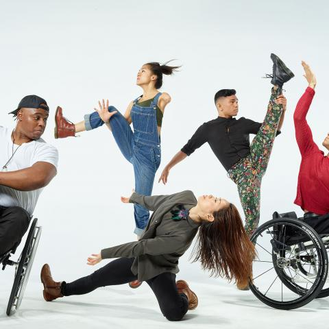 Five dancers, two of which are in wheelchairs, dance in front of a white backdrop.