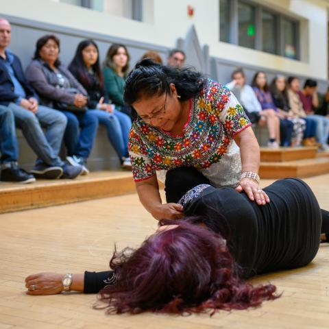 An audience watches as a woman performs assisting another woman, who lies on the ground.