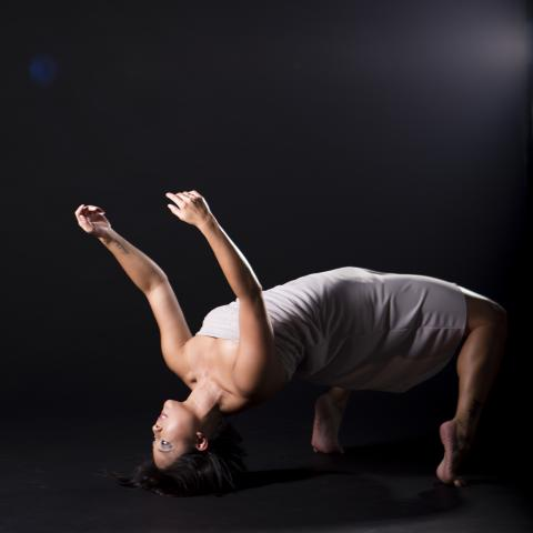 A dancer rests on their head and feet, with their torso extended.