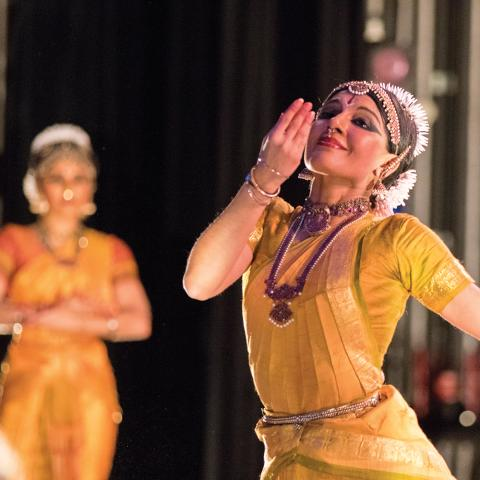 A woman in traditional Indian garb and decoration performs with others similarly adorned.