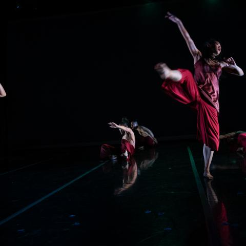 Three dancers, in red outfits, leap.