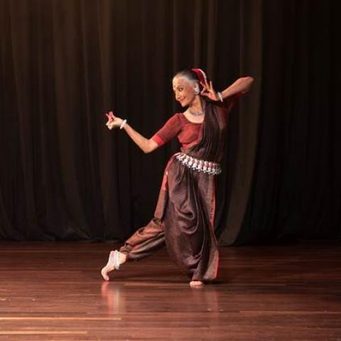 Bijayini dances in front of a brown curtain, in traditional Indian garb.