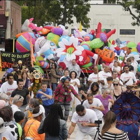 A crowded street with performers and large inflatables.