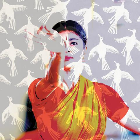 A woman in orange and yellow traditional Indian dress gestures with her hand at images of crows