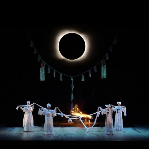 On dark stage, lit by an eclipse-like orb, four dancers in all white perform in front of Jin Hi who plays a string instrument behind them.