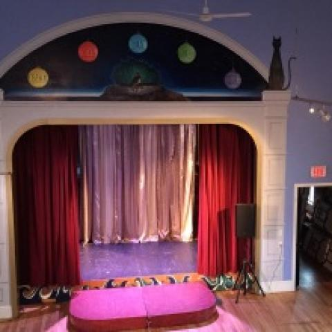 a cute proscenium stage in a giant purple room