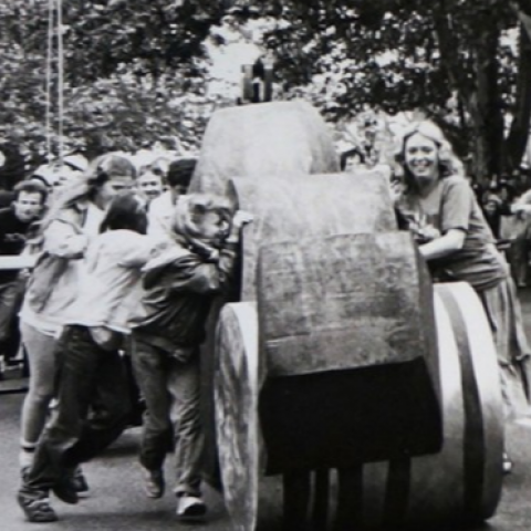 In black and white: women push sculptures on wheels down a street.