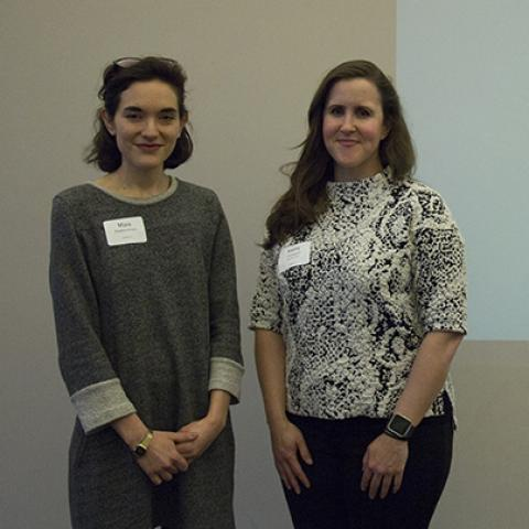 Two women pose in front of a slide from their presentation