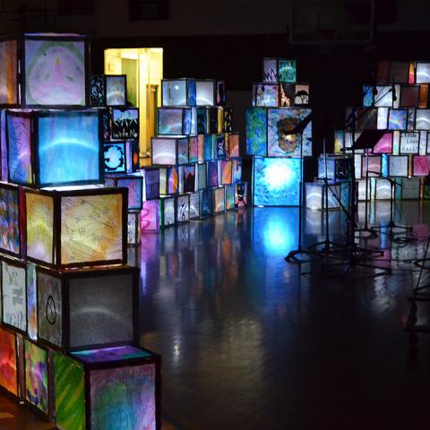 Illuminated cubes are stacked on top of each other in various pyramid/wall formations within a cavernous dark space.