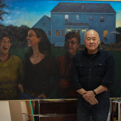 Wen-ti poses in front of one of his painting. A painting of women in the yard of a house at twilight.